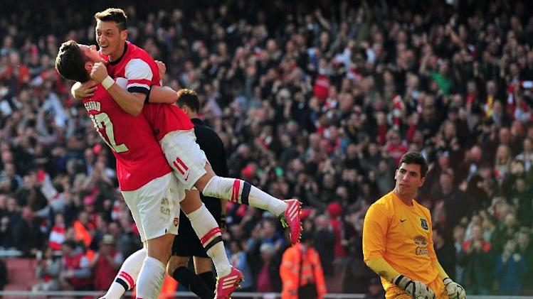 Arsenal midfielder Mesut Ozil (C) is picked up by striker Olivier Giroud after scoring the fourth goal during their English FA Cup quarter-final against Everton at the Emirates Stadium in London on March 8, 2014