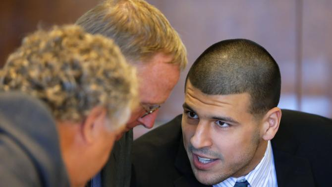 Aaron Hernandez, former player for the NFL's New England Patriots football team, talks to defense attorneys Michael Fee and Charles Rankin during a court appearance at the Bristol County Superior Court in Fall River