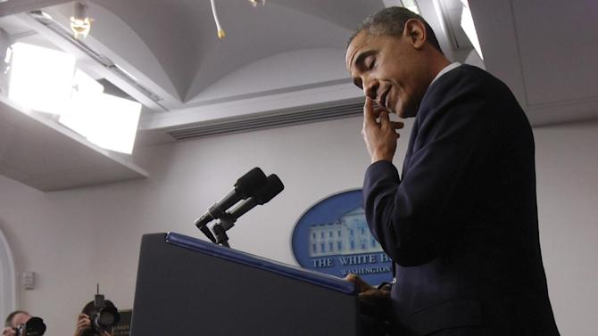 President Barack Obama wipes his eye as he speaks about the school shooting in Newtown, Conn., Friday, Dec. 14, 2012, in the briefing room of the White House in Washington. (AP Photo/Charles Dharapak)