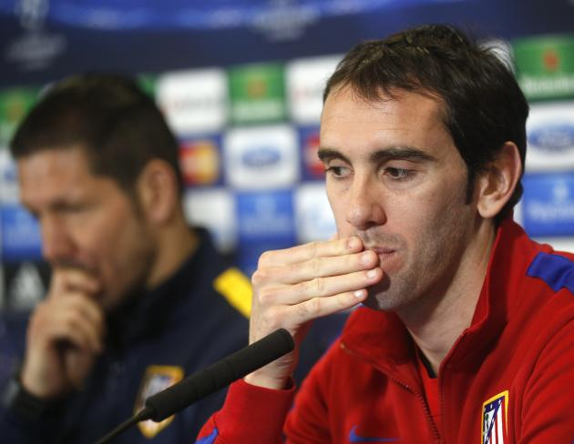 Atletico Madrid's Diego Godin gestures next to coach Diego Simeone during a news conference at the Vicente Calderon stadium in Madrid