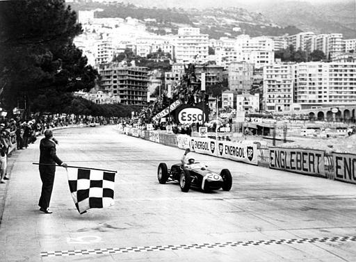 Stirling Moss of Britain raises his hand in victory after passing the finish line in first place at the Monaco Grand Prix Automobile race on May 14, 1961. The checked flag goes down on the circuit in the foreground. Moss is driving a Lotus sports car. (AP Photo)