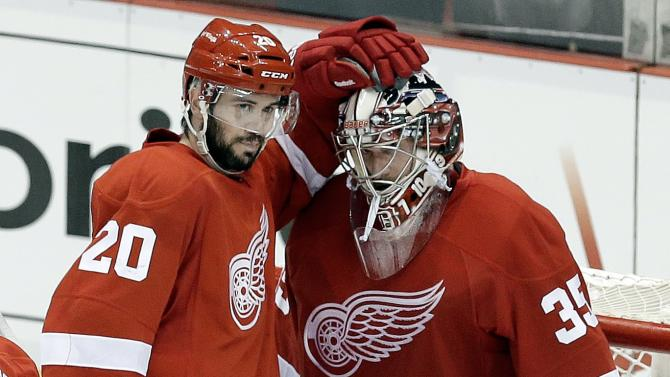 Detroit Red Wings left wing Drew Miller (20) congratulates goalie Jimmy Howard (35) after beating the Chicago Blackhawks 3-1 after a NHL hockey Stanley Cup playoffs Western Conference semifinal game in Detroit, Monday, May 20, 2013. (AP Photo/Paul Sancya)