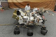 Jet Propulsion Laboratory (JPL) engineers examine a full size engineered model of the Mars rover Curiosity at JPL in Pasadena, California August 2. Imagine taking 400 scientists on an alien road trip where each one wants to examine every interesting rock along the way. Welcome to the next two years of NASA's landmark robotic mission on Mars