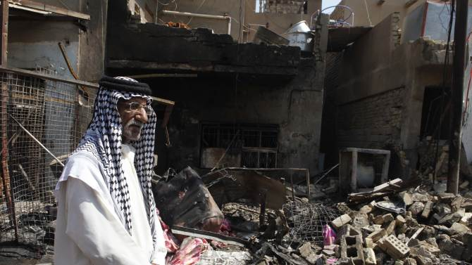 A man stands in front of the scene of a bomb attack in Madain, about 15 miles (25 kilometers) southeast of Baghdad, Iraq, Monday, July 23, 2012. An onslaught of bombings and shootings killed scores of people across Iraq on Monday, in the nation's deadliest day so far this year. The attacks come days after the leader of al-Qaida in Iraq declared a new offensive seeking to re-assert its might in the security vacuum left by the departing Americans. (AP Photo/Karim Kadim)
