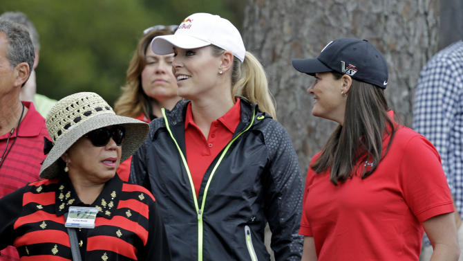 Tiger Woods' mother Kultida Woods, left, skier Lindsey Vonn and her physical therapist Lindsay Winninger, right, watch Woods during the fourth round of the Masters golf tournament Sunday, April 14, 2013, in Augusta, Ga. (AP Photo/David J. Phillip)