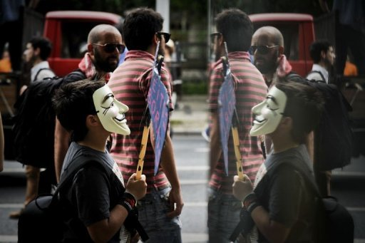 "<p>An ""Indignant"" demonstrator, wearing a Guy Fawkes mask, is reflected on a window as he protests in downtown Lisbon on May 12. Thousands of Portuguese took to the streets of Lisbon in a new protest against government financial policies expected to get even tougher to meet pledges to creditors.</p>"