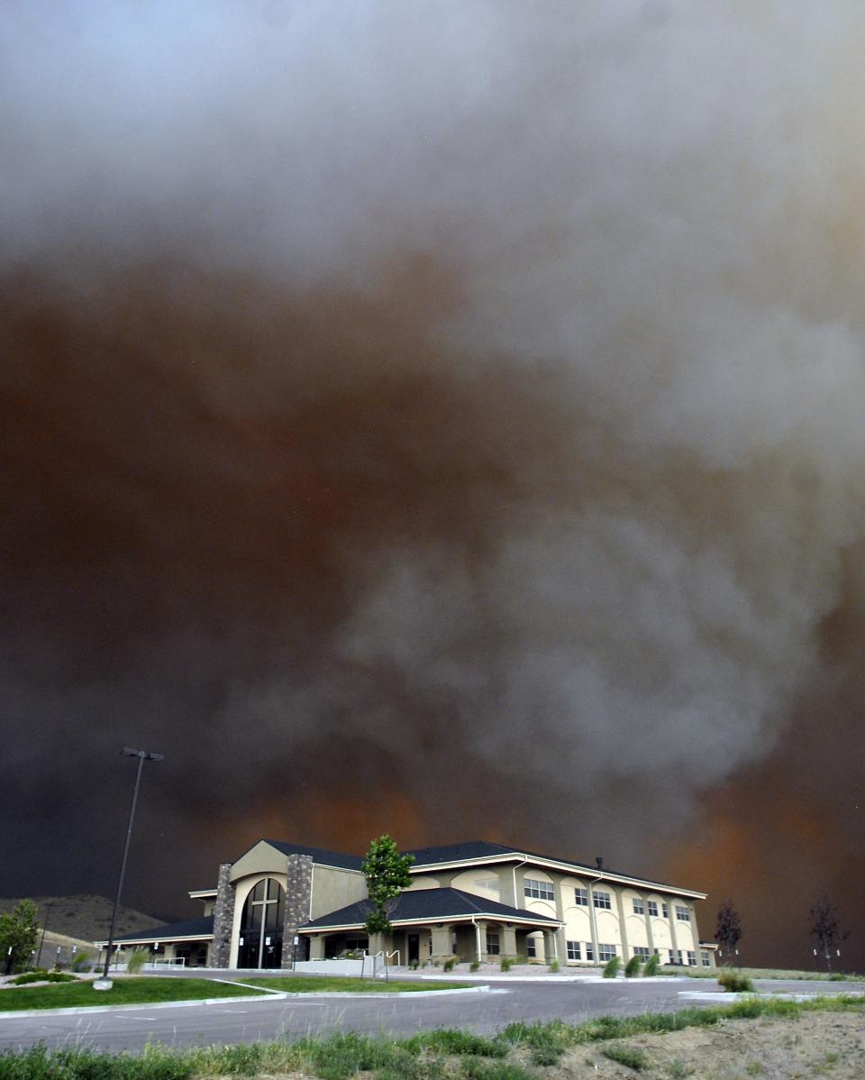 The skies are black and glow orange from as the Waldo Canyon Fire which races through portions of Colorado Springs, Colo. on Tuesday, June 26, 2012 leaving a trail of destruction, burning homes and buildings in its path. Heavily populated areas in the fire's path have been affected.   (AP Photo/Bryan Oller)