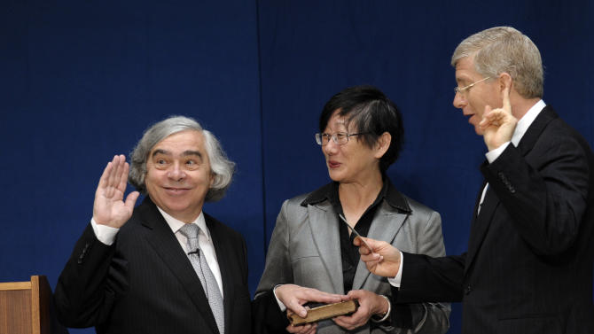 Dr. Ernest Moniz, left, responds to a noise as he stands with his wife Naomi, center, as Deputy Energy Deputy Secretary Daniel Poneman, right, administers the oath of office to Moniz who was sworn in as Energy Secretary of Energy, Tuesday, May 21, 2013, during a ceremony at the Energy Department in Washington. (AP Photo/Susan Walsh)