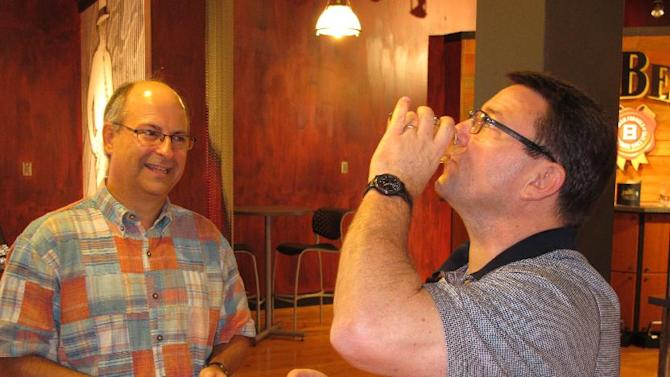 This Oct. 3, 2012 photo shows Tim Allen, of Fuquay-Varina, N.C., sampling one of Jim Beam's bourbons as his college buddy Woody Parker looks on during a tour of the Beam distillery in Clermont, Ky. (AP Photo/Bruce Schreiner)