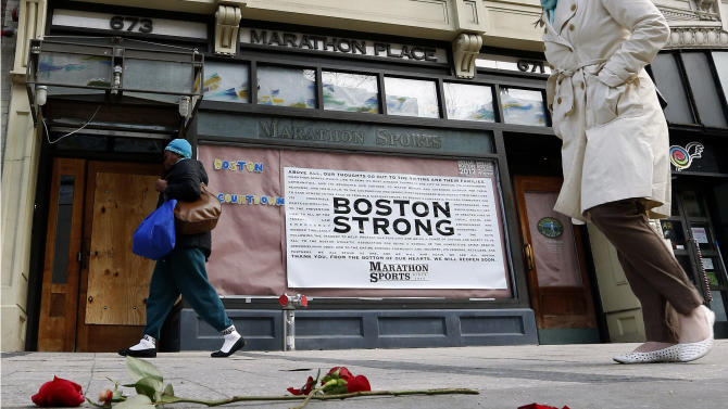 Pedestrians pass the spot where the first bomb detonated on Boylston Street near the finish line of the Boston Marathon Wednesday, April 24, 2013, in Boston. Traffic was allowed to flow all the way down Boylston Street on Wednesday morning for the first time since two explosions killed 3 people and injured many on April 15. (AP Photo/Michael Dwyer)