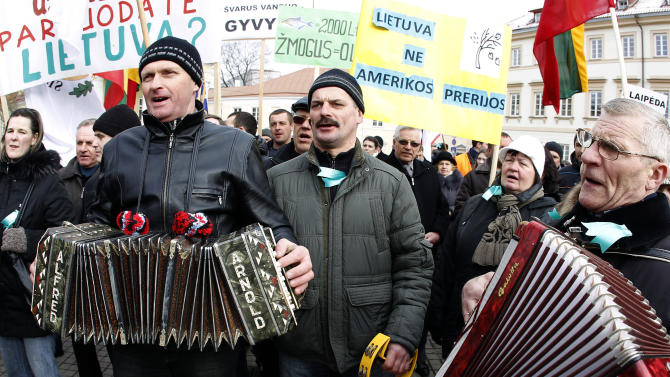 """Lithuanians gathered for an anti-American demonstration rally at the President  palace in Vilnius, Lithuania,Tuesday, Feb. 26, 2013. Protesters oppose government plans to explore shale gas fields in the western part of the country.  Poster background right reads - """" Lithuania is not American Prairies."""" (AP Photo/Mindaugas Kulbis)"""
