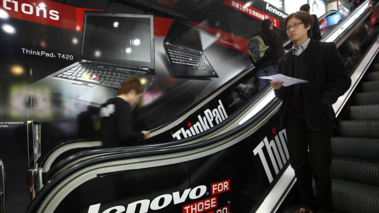 People take escalators bearing advertisement of Lenovo computer at a shopping center in Hong Kong Thursday, Feb. 9, 2012. Lenovo Group Ltd., the world's second biggest personal computer maker, said Thursday that quarterly profit grew by more than half but warned hard drive costs would remain high amid a global shortage. (AP Photo/Kin Cheung)