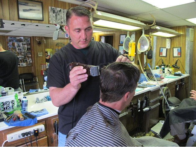 In this May 23, 2013, photo, barber BJ McClead, whose daughter Hayden was a friend of slain 16-year-old Skylar Neese, cuts a customer's hair at John's Barber Shop in Star City, W.Va. People in the sma