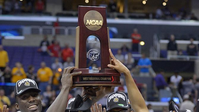 Wichita State's Carl Hall (22) and teammates pose with the regional trophy after defeating Ohio State 70-66 in the West Regional final in the NCAA men's college basketball tournament, Saturday, March 30, 2013, in Los Angeles. (AP Photo/Mark J. Terrill)