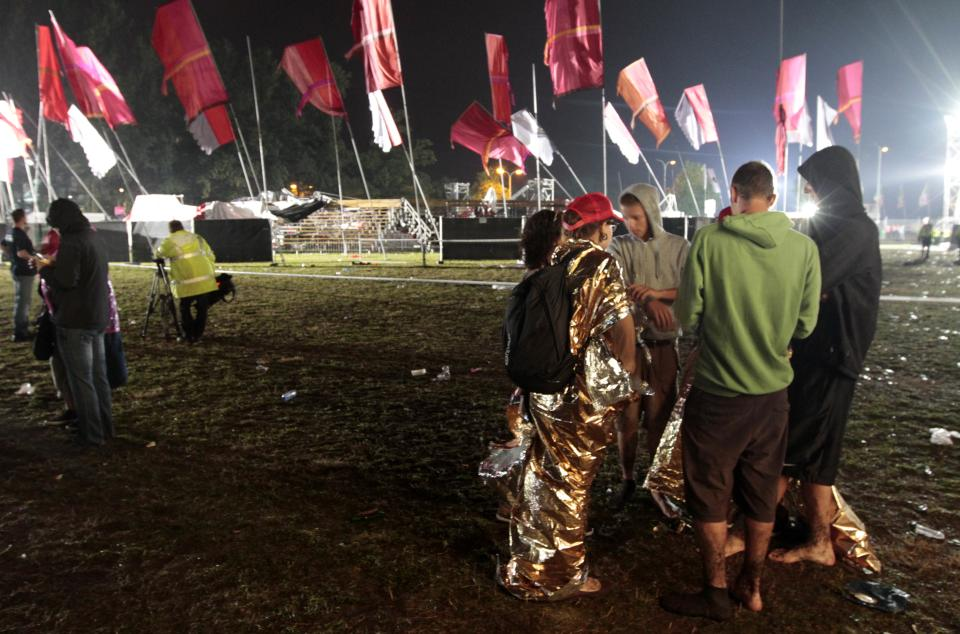 Music fans walk near to a collapsed tent  after a storm swept through an open air music festival near Hasselt, about 50 miles (80 kilometers) east of Brussels, Belgium, Thursday, Aug. 18, 2011. The storm killed at least three people and injured over 70 others, an official said.  (AP Photo/Yves Logghe)