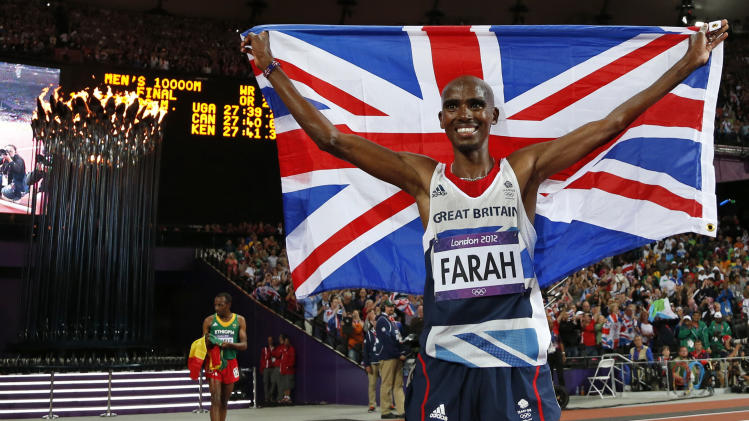 Britain's Mo Farah celebrates winning gold in the men's 10,000-meter final as the Olympic flame is seen in the background during the athletics in the Olympic Stadium at the 2012 Summer Olympics, London, Saturday, Aug. 4, 2012. (AP Photo/Matt Dunham)
