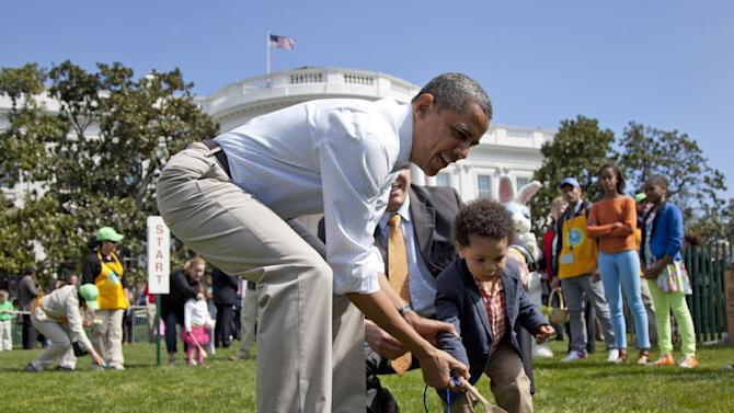 President Barack Obama helps a little boy roll his egg to the finish line during the annual White House Easter Egg Roll, Monday, April 9, 2012, on the South Lawn of the White House in Washington.  In the background, at left are Malia Obama and Sasha Obama. (AP Photo/Carolyn Kaster)