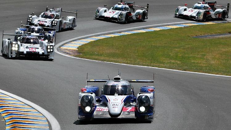 The Toyota TS040 Hybrid driven by Japanese driver Kazuki Nakajima, France's Stephane Sarrazin and Austria's Alexander Wurtz, foreground, takes a bend during the 82th 24-hour Le Mans endurance race, in Le Mans, western France, Saturday, June 14, 2014. (AP Photo/Bob Edme)