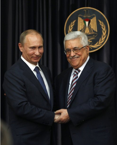Palestinian President Abbas shakes hands with his Russian counterpart Putin during news conference in Bethlehem