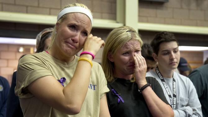 Firefighters Kayla Garst, left, and Darce Knight react during a memorial service, Monday, July 1, 2013 in Prescott, Ariz. The service was held for the 19 Granite Mountain Hotshot Crew firefighters who were killed Sunday, when an out-of-control blaze overtook the elite group. (AP Photo/Julie Jacobson)