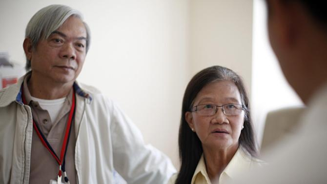 Patient Kim Nguyen, right, and her husband Quang Nguyen are seen at National Institute of Health in Bethesda, Md., Wednesday, Aug. 22, 2012.  Researchers have identified a mysterious new disease that has left scores of people in Asia and some in the United States with AIDS-like symptoms even though they are not infected with HIV. The patients' immune systems become damaged, leaving them unable to fend off germs as healthy people do. Kim Nguyen, 62, a seamstress from Vietnam who has lived in Tennessee since 1975, may have been in danger of that when she first sought help for a persistent fever, infections throughout her bones and other bizarre symptoms in 2009. She had been sick off and on for several years and had visited Vietnam in 1995 and again in early 2009. (AP Photo/Pablo Martinez Monsivais)