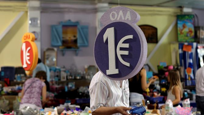 """Customers browse discounted goods for sale at a """"one euro store"""" in Athens, on Monday, June 18, 2012. Europe looked on with wary relief Monday as Greek conservative leader Antonis Samaras received a mandate to launch coalition talks after coming first in national elections that follow weeks of uncertainty over the debt-crippled country's future in the continent's joint currency. (AP Photo/Petros Giannakouris)"""