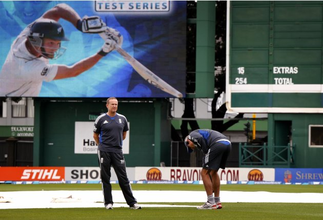 England's captain Cook inspects the pitch with team coach Flower on final day second test against New Zealand in Wellington