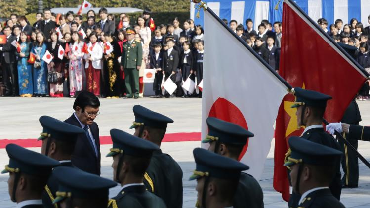 Vietnam's President Truong bows to the national flags of Vietnam and Japan during a welcoming ceremony at the Imperial Palace in Tokyo