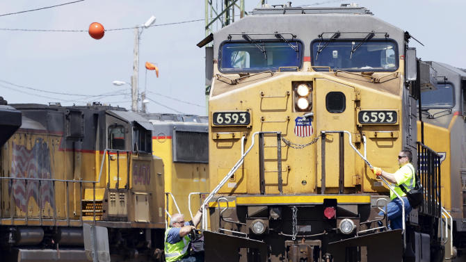 FILE - In this June 6, 2014 photo, a train operator, left, dismounts a Union Pacific locomotive, while another operator climbs up, at a rail yard in Council Bluffs, Iowa. Union Pacific reports quarterly financial results on Thursday, Oct. 23, 2014. (AP Photo/Nati Harnik, File)