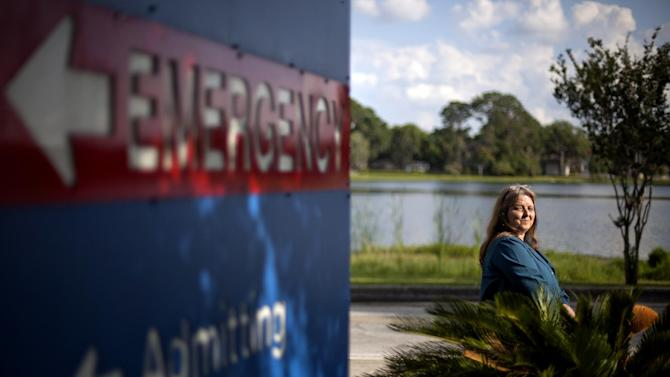 In this photo taken Monday, May 14, 2012, Kathy Watson sits outside Shands Lake Shore Hospital, where she receives her cancer treatment and also picks up patients for her medical transport company, in Lake City, Fla. Watson voted Republican in 2008 and believes the government has no right telling Americans to get health insurance. Nonetheless, she says she'd be dead if it weren't for President Barack Obama's health care law. (AP Photo/David Goldman)