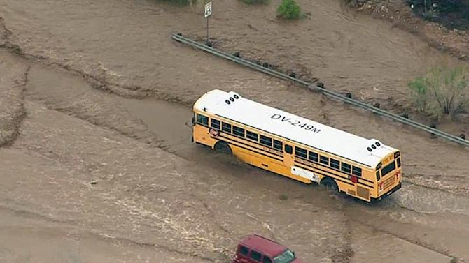 In this image made from a video provided by ABC15 TV, a school bus navigates a flooded road north of Phoenix, Tuesday, Aug. 19, 2014. It was not known if there were children aboard the bus at the time. The area was flooded after several inches of rain pummeled the state. (AP Photo/ABC15 TV)