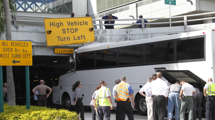 Workers and law enforcement officers prepare to remove a bus after it hit a concrete overpass at Miami International Airport in Miami on Saturday, Dec. 1, 2012. The vehicle was too tall for the 8-foot-6-inch entrance to the arrivals area, and buses are supposed to go through the departures area which has a higher ceiling, according to an airport spokesperson. (AP Photo/Wilfredo Lee)