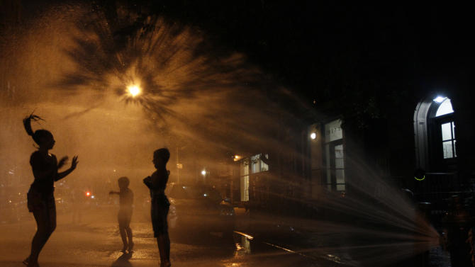 Vanity Mendez, 11, left, Isaiah Rivera, 6, center,  and Jonathan Medina, 11, cool off at an open fire hydrant in the East Village neighborhood of Manhattan, Thursday, July 21, 2011.  A heatwave that has enveloped much of the central part of the country for the past couple of weeks is moving east and temperatures are expected to top the 100-degree mark. (AP Photo/Mary Altaffer)