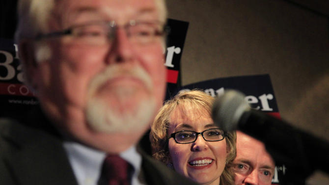 In an election to fill former Rep. Gabrielle Giffords, D-Ariz., congressional seat, Democratic candidate Ron Barber, left, shrugs as he celebrates a victory with supporters, including Giffords, middle, and Giffords husband, Mark Kelly, right, at a post election event, Tuesday, June 12, 2012, in Tucson, Ariz.  Gabrielle Giffords' former district director, in a special election for the seat Giffords left in January to focus on her recovery from a gunshot wound to her head during a gunman's shooting spree a year earlier.(AP Photo/Ross D. Franklin, pool)