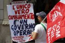 A member of Italy&amp;#039;s metalworkers union Fiom read a banner during a demonstration in Rome