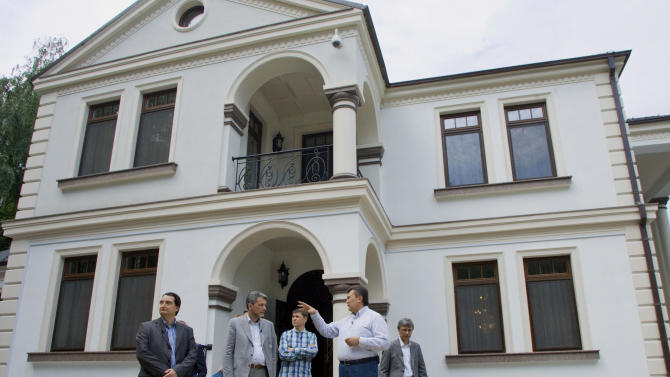 In this photo taken Friday, June 24, 2011, during a tour organized by the Ukrainian Presidential press-service, President Viktor Yanukovych, right, talks to journalists he's invited to see his official residence called Mezhygirya, outside Kiev, Ukraine. But his critics point to strong evidence he actually lives in a different more luxurious building. (AP Photo/Mykhailo Markiv, Presidential Press Service)