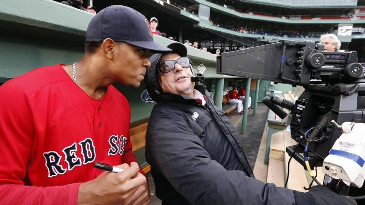 Boston Red Sox's Xander Bogaerts examines a television camera before a baseball game against the Baltimore Orioles in Boston, Friday, April 18, 2014. (AP Photo/Michael Dwyer)