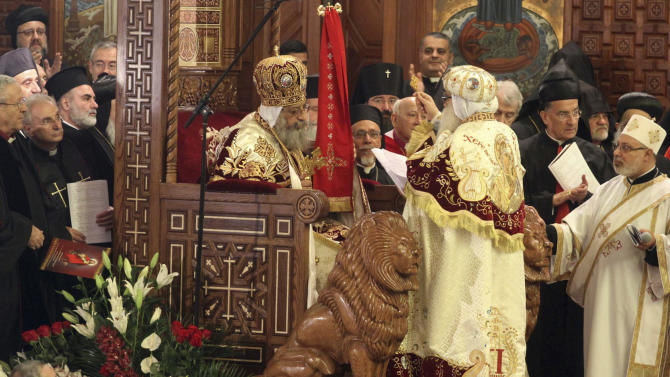 Pope Tawadros II, 60, sits on the throne of St. Mark, the Coptic church's founding saint, wearing the papal crown, during an elaborate ceremony lasting nearly four hours, attended by the nation's Muslim prime minister and a host of Cabinet ministers and politicians, in the Coptic Cathedral in Cairo, Egypt, Sunday, Nov. 18, 2012. Tawadros did not address the televised ceremony, but had a brief speech read on his behalf by one of the church's leaders in which he pledged to work for the good of Egypt, with its Muslims and Christians alike.  (AP Photo/Sami Wahib)
