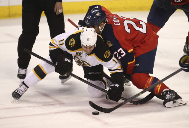 Boston Bruins' Gregory Campbell (112) and Florida Panthers' Scott Gomez (23) battle for the puck during the third period of an NHL hockey game in Sunrise, Fla., Sunday, March 9, 2014. Boston w