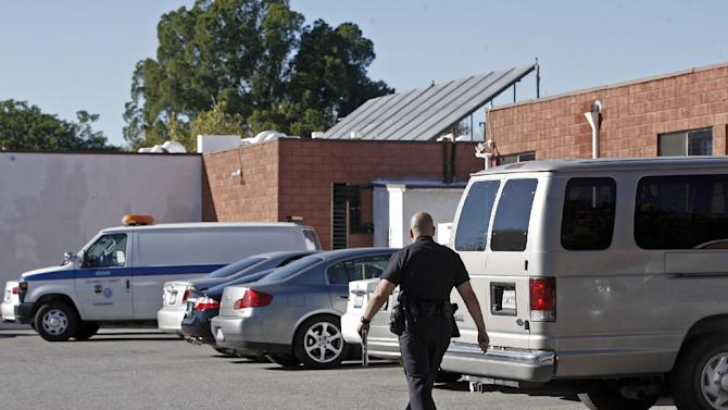 A Los Angeles police officer walks toward a coroner's van at the Country Villa Sheraton nursing facility in the North Hills area of Los Angeles Wednesday, Dec. 11, 2013. Police say a 60-year-old man, Lance Holger Anderson of suburban Santa Clarita, has been booked for investigation of murder in the shootings of his dementia-stricken wife and his sister, who was in a vegetative state at a nursing home. (AP Photo/Nick Ut)