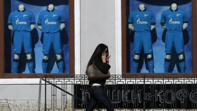 Woman passes by shop window displaying Zenit's jerseys with a logo of Gazprom in St. Petersburg