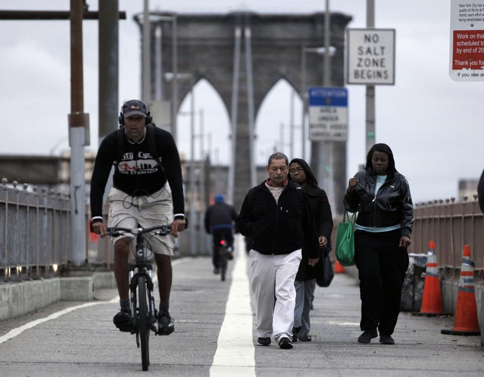 Morning commuters walk and bicycle across New York's Brooklyn Bridge, Wednesday, Oct. 31, 2012. On the Brooklyn Bridge, closed earlier because of high winds, joggers and bikers made their way across the span before sunrise. Car traffic on the bridge was busy, and slowed as it neared Manhattan. (AP Photo/Richard Drew)
