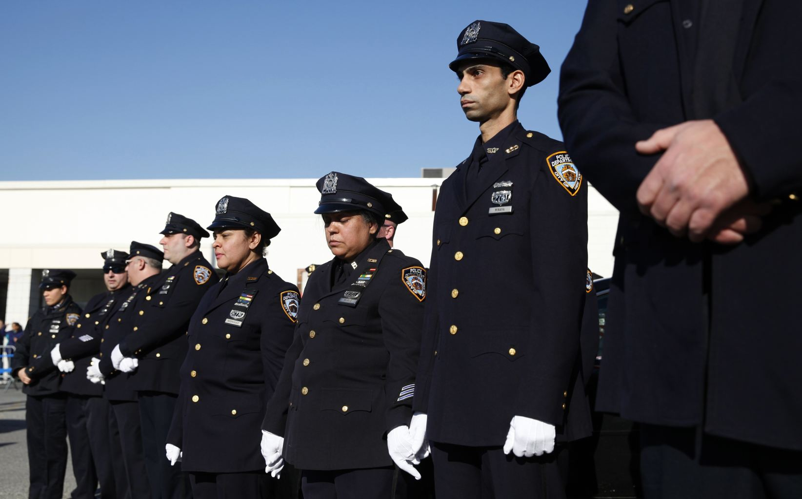 New york city police stand in silence as they listen to the funeral