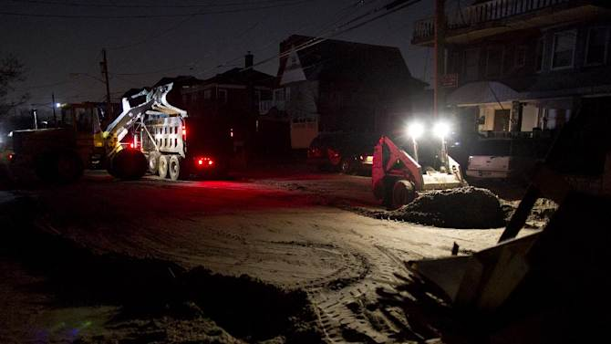 A front loader works to remove sand and debris as night falls on the Rockaway neighborhood in the Queens borough of New York, Sunday, Nov. 11, 2012, in the wake of Superstorm Sandy. (AP Photo/Craig Ruttle)