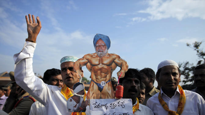 "Activists of Telugu Desam Party (TDP) carry a caricature of Indian Prime Minister Manmohan Singh with the words ""the blood suckers are not human beings but devils"" during a protest at a bus station in Hyderabad, India, Thursday, Sept. 20, 2012. Angry opposition workers have disrupted train services as part of a daylong strike in India to protest rising diesel prices and the government's decision to open the country's huge retail market to foreign companies. (AP Photo/Mahesh Kumar A.)"