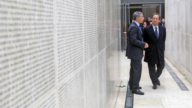 Socialist presidential candidate for the upcoming presidential election Francois Hollande, right, listens to Memorial director Jacques Fredj as he stands by the wall engraved  with the names of the 76,000 Jews deported from France as part of the Nazi plan to exterminate Judaism in Europe, during a visit to the Shoah Memorial in Paris, Sunday, April 29, 2012. (AP Photo/Jacky Naegelen/Pool)