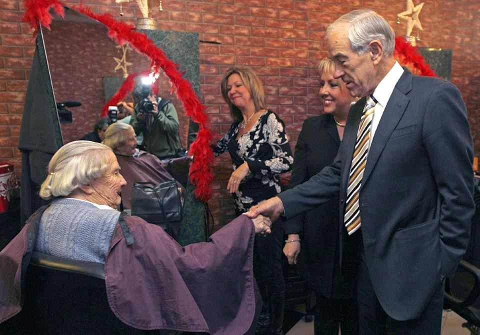 Republican presidential candidate Rep. Ron Paul, R-Texas, right, shakes hands with Helen Taylor, of Durham, N.H., while campaigning at a hair salon in Exeter, N.H., Tuesday Dec. 20, 2011. (AP Photo/Charles Krupa)