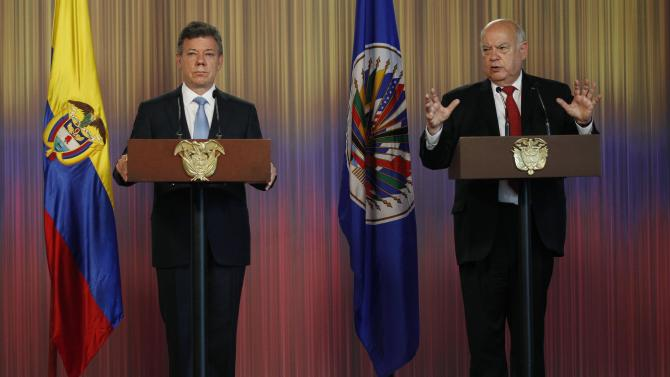 OAS chief Jose Miguel Insulza, right, talks to the media during a joint press conference about a regional study on the illicit drug trade, presented by Insulza to Colombia's President Juan Manuel Santos, left, at the Presidential Palace in Bogota, Colombia, Friday, May 17, 2013. The  $2.2 million study which emphasizes drug abuse as primarily a public health issue, makes no firm recommendations, instead suggesting several possible ways to stem the illicit drug trade, which has fueled violent crime and corruption and even destabilized governments. (AP Photo/Fernando Vergara)