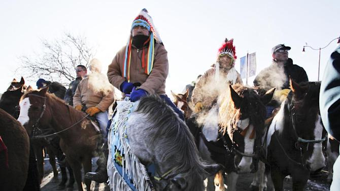 "Riders Gus High Eagle, center left, and Carl Mazawasicuna, center right, both of Canada, sat on their horses and listened in following The Dakota Wokiksuye Memorial Ride during a ceremony at Reconciliation Park, Wednesday, Dec. 26, 2012, in Mankato, Minn. The annual ride commemorates the 38 + 2 Dakota warriors hanged following the Dakota War of 1862. The ""Dakota 38"" Memorial lists the names of all the Dakota warriors hanged in 1862. (AP Photo/The Star Tribune, David Joles)"