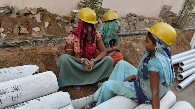 Female labourers wearing helmets take a break from laying underground electricity cables along a roadside in Ahmedabad, India